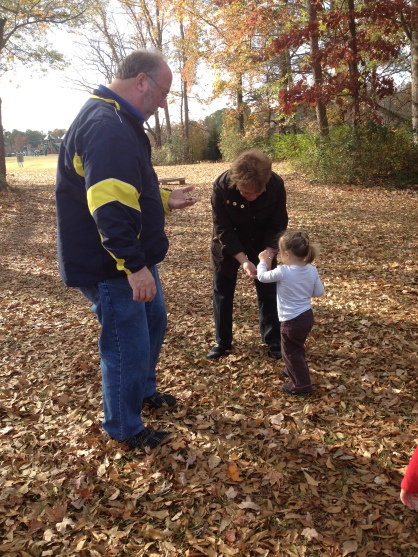 Elodie collecting acorns with her grandparents